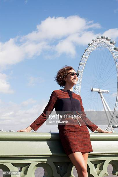 smiling woman leaning on railing of bridge in front of ferris wheel - london eye stock photos and pictures