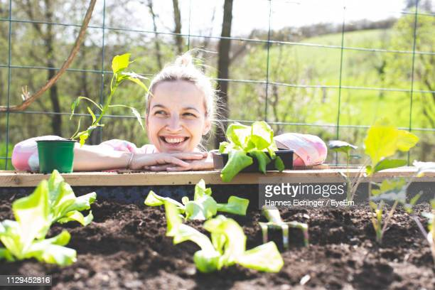 smiling woman leaning on raised bed in yard - gärtnern stock-fotos und bilder
