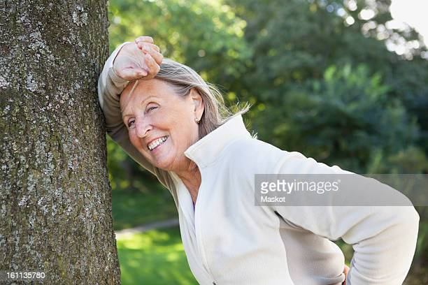 Smiling woman leaning on tree trunk
