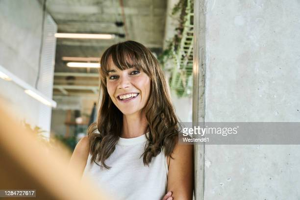 smiling woman leaning on wall while standing at home - braunes haar stock-fotos und bilder