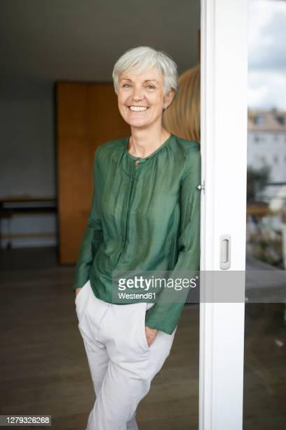 smiling woman leaning on window with hands in pockets - hände in den taschen stock-fotos und bilder
