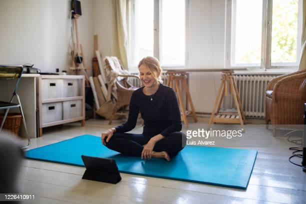 smiling woman learning yoga through digital tablet - barefoot stock pictures, royalty-free photos & images