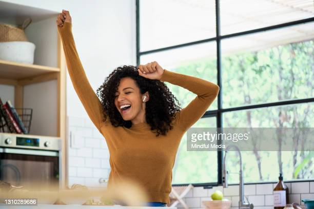 smiling woman listening music and dancing in kitchen - mid adult women stock pictures, royalty-free photos & images
