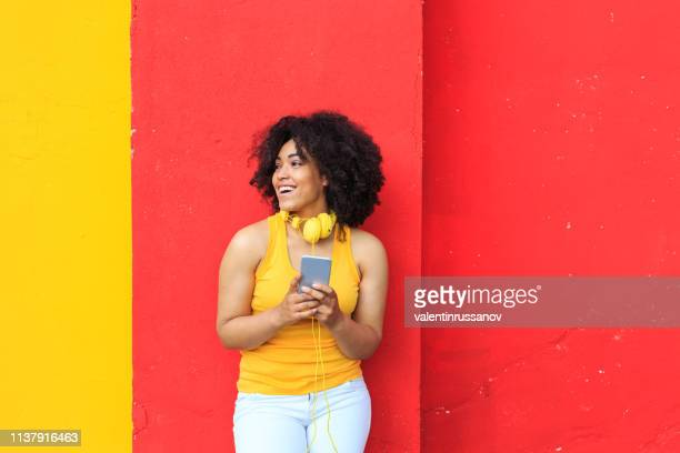 smiling woman listening music and using smart phone - bright colour stock pictures, royalty-free photos & images