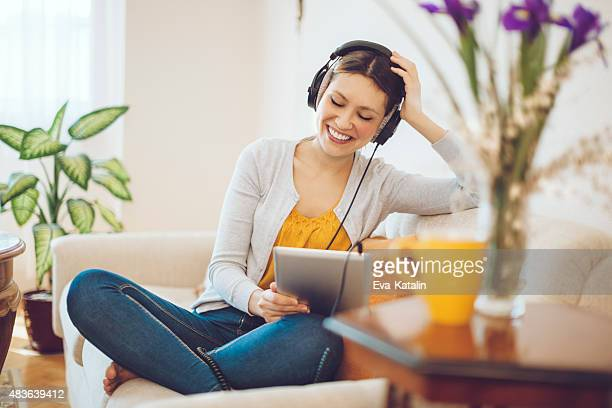 smiling woman listening music at home - serene people stock pictures, royalty-free photos & images