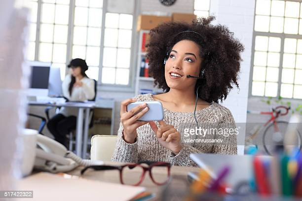 Smiling woman listening music on her telephone