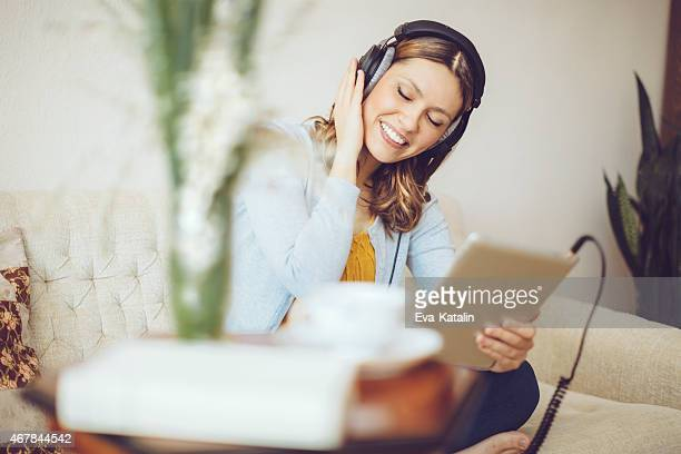 Smiling woman listening to music at home
