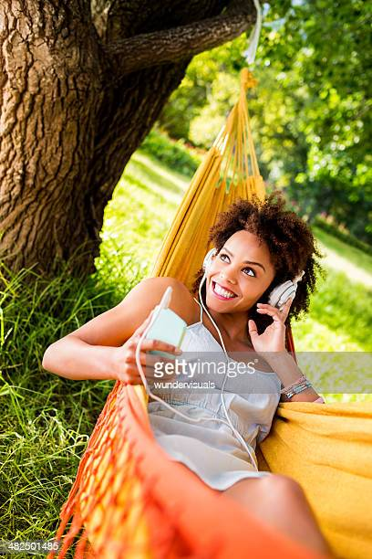 Smiling woman listening to music in hammock