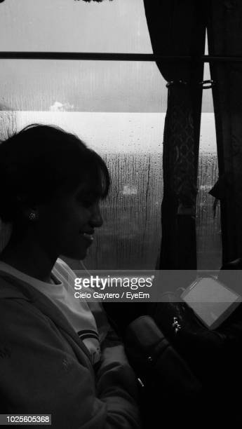 Smiling Woman Listening To Music On Headphones While Sitting In Bus