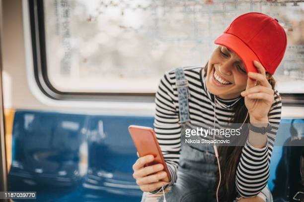 smiling woman listening to music on smart phone in subway - red hat stock pictures, royalty-free photos & images