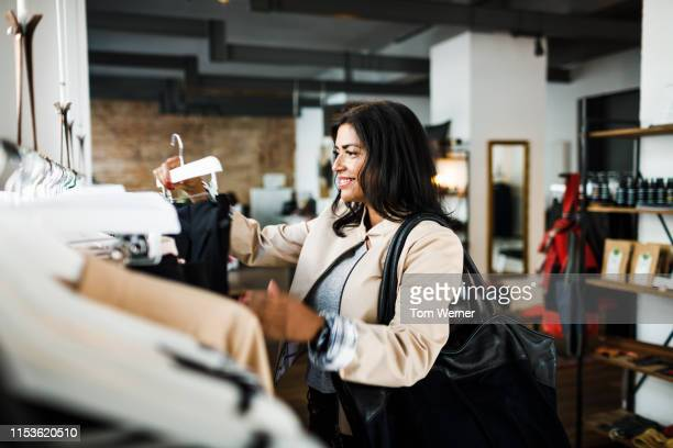 smiling woman looking a clothing on display - jacket stock pictures, royalty-free photos & images