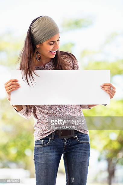 Smiling woman looking at a blank placard