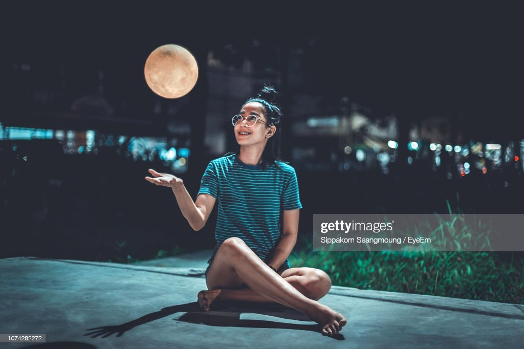 Smiling Woman Looking At Artificial Moon While Sitting On Footpath At Night : Stock Photo
