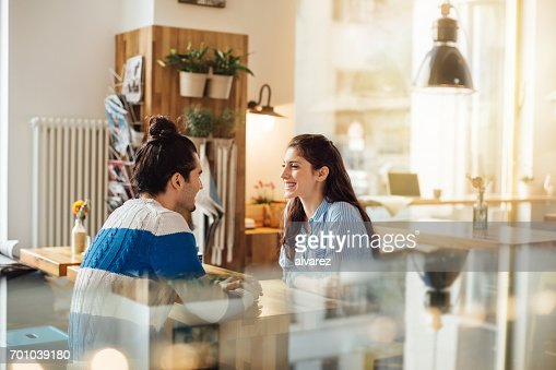 Smiling woman looking at boyfriend in coffee shop