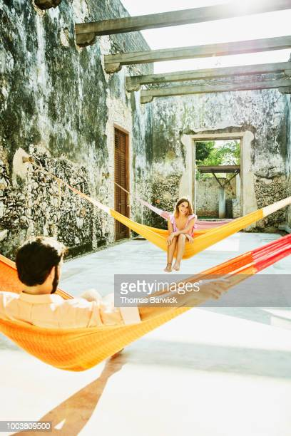 Smiling woman looking at boyfriend while relaxing in hammock at luxury resort