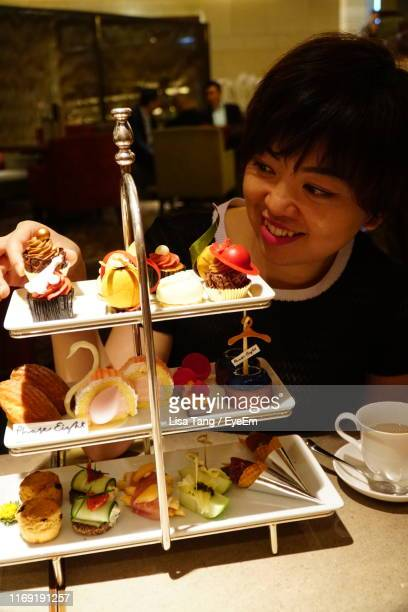 smiling woman looking at cakes on table - lisa tang stock photos and pictures