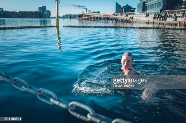 smiling woman looking at camera and cold water swimming in denmark - copenhagen stock pictures, royalty-free photos & images