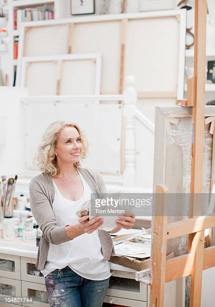 Smiling woman looking at canvas in art studio