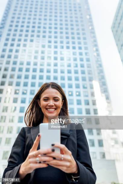 Smiling woman looking at cell phone in the city