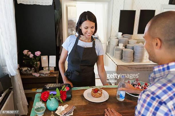 Smiling woman looking at desert while man standing by counter in cafe