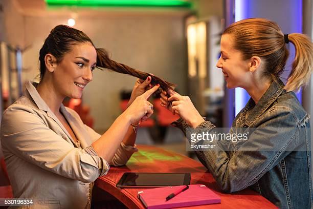 Smiling woman looking at friends hair at beauty salon.