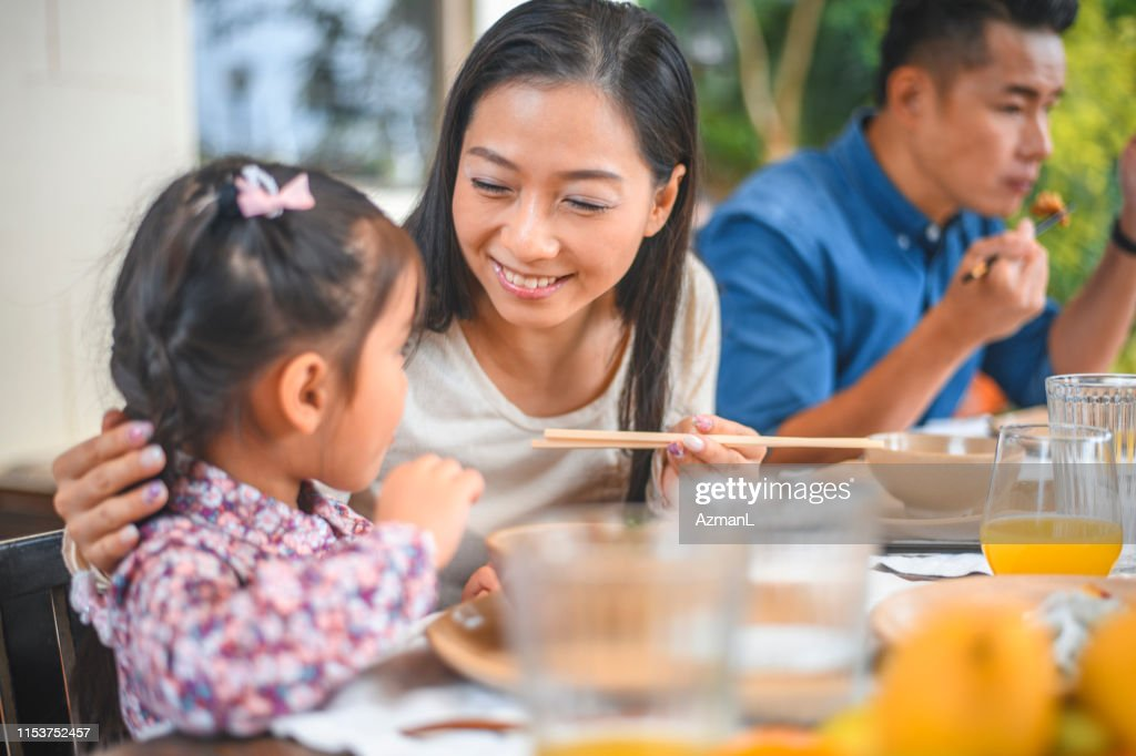 Smiling woman looking at girl eating in back yard : Stock Photo