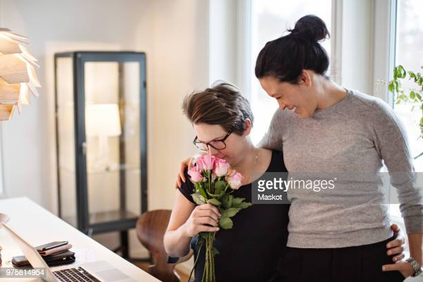 smiling woman looking at girlfriend smelling pink roses at home - faro sweden - fotografias e filmes do acervo