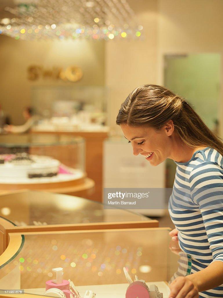 Mulher sorridente olhar para jóias em caso de visualização : Foto de stock