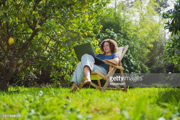 smiling woman looking at laptop while sitting on chair in permaculture garden - albero da frutto foto e immagini stock