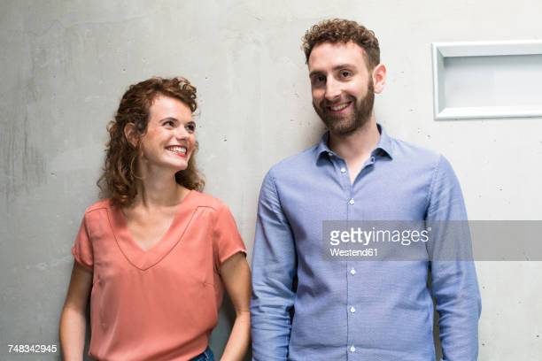 smiling woman looking at man at concrete wall - two people stock-fotos und bilder