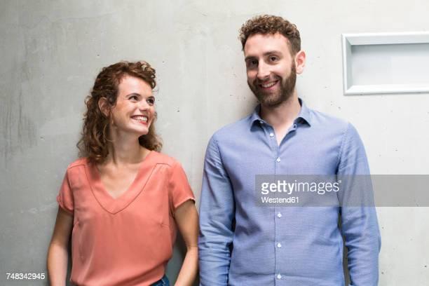 smiling woman looking at man at concrete wall - zwei personen stock-fotos und bilder