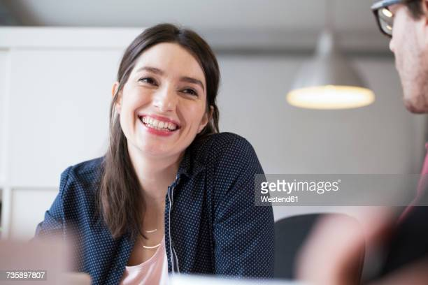 Smiling woman looking at man in office