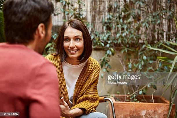 smiling woman looking at man in yard - dos personas fotografías e imágenes de stock