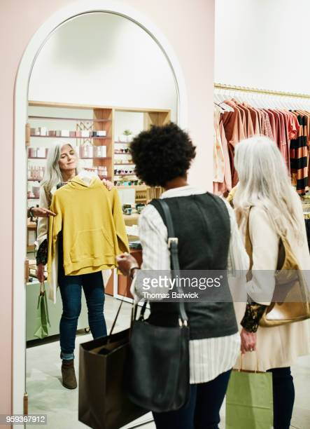 smiling woman looking at shirt in mirror while shopping with friend in clothing boutique - older women in short skirts stock pictures, royalty-free photos & images