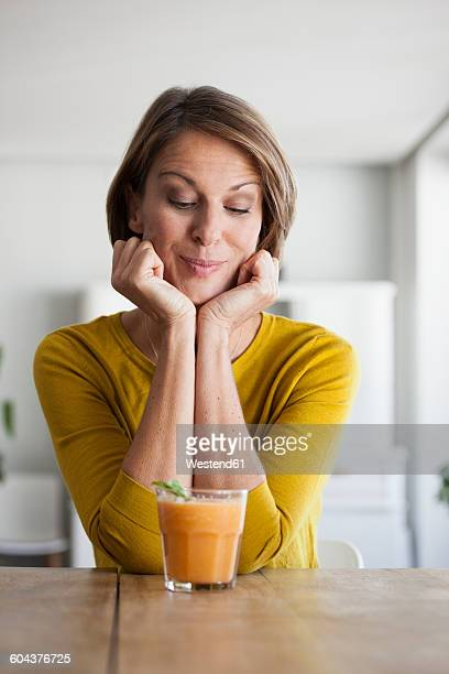 smiling woman looking at smoothie - one mature woman only stock-fotos und bilder