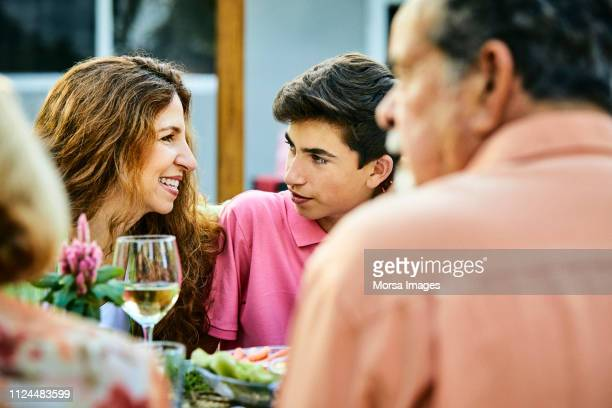 smiling woman looking at son during garden party - celebration fl stock pictures, royalty-free photos & images