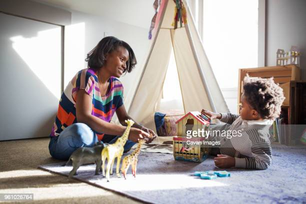 smiling woman looking at son while playing with toys in bedroom - toy animal stock photos and pictures