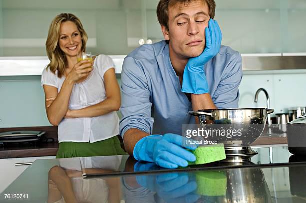 smiling woman looking at sulking man holding sponge - bestrafung stock-fotos und bilder