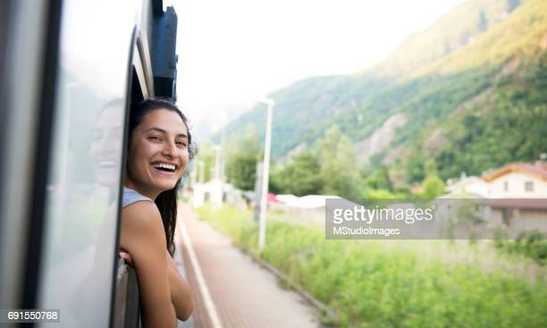 Smiling woman looking at the view from train.