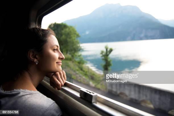 lächelnde frau betrachten aus zug - weite landschaft stock-fotos und bilder