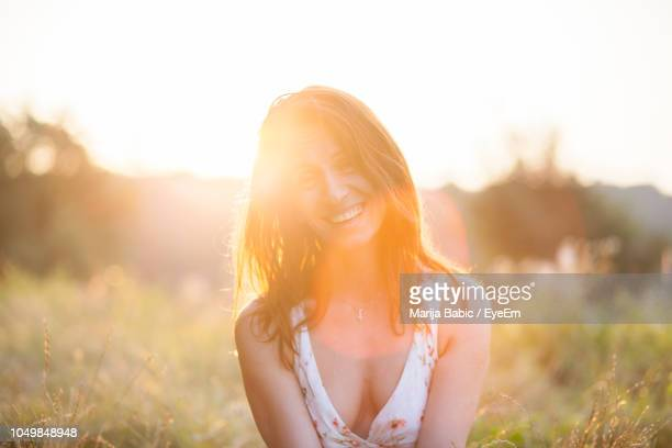 smiling woman looking away against sky during sunset - cleavage stock pictures, royalty-free photos & images