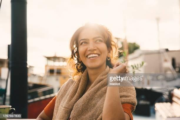 smiling woman looking away in houseboat - stockholm stock-fotos und bilder