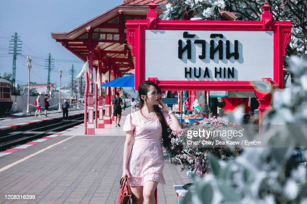 smiling woman looking away while standing on railroad station platform - hua hin thailand stock pictures, royalty-free photos & images