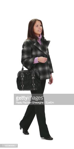 smiling woman looking away while walking against white background - people stock pictures, royalty-free photos & images