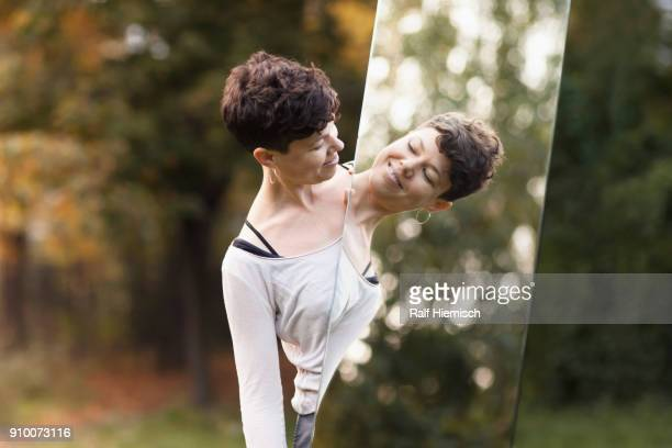 Smiling woman looking in mirror while standing at park