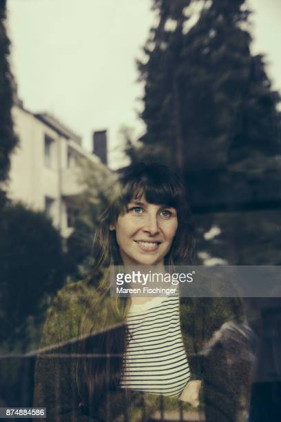 Smiling woman looking out of window