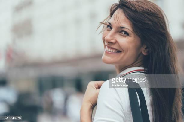 mulher sorridente, olhando por cima - mulheres de idade mediana - fotografias e filmes do acervo