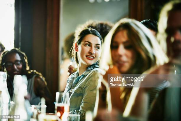 Smiling woman looking over shoulder while sitting in bar with friends