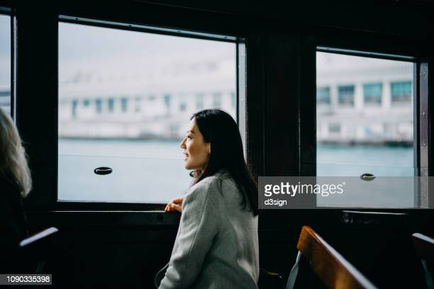 smiling woman looking through window and enjoying the spectacular city skyline of hong kong while riding on star ferry - ferry stock pictures, royalty-free photos & images