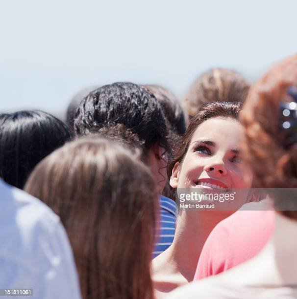Smiling woman looking up in crowd